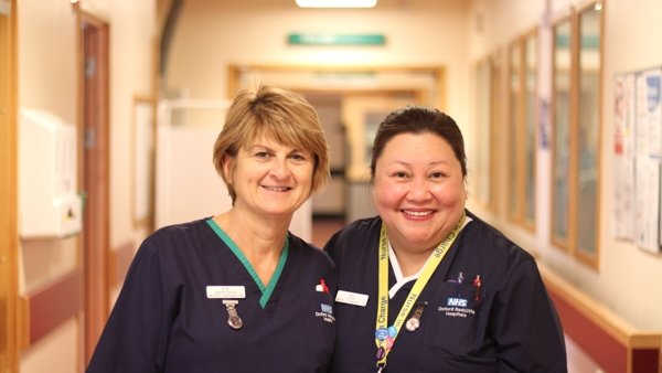 Two smiling uniformed nurses in a ward corridor