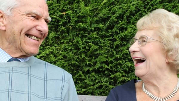 Two elderly people looking happily at each other