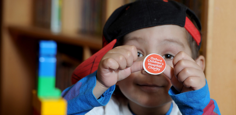 Young patient at Oxford Childrens Hospital plays with Oxford Childrens Hospital Charity sticker to promote fundraising